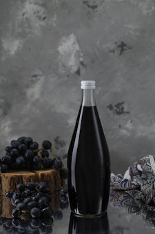 Wine bottle with grapes on wooden piece