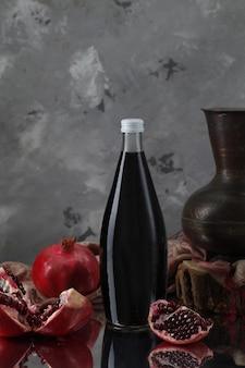 Bottiglia di vino con melograni, vaso su sciarpa e pezzo di legno