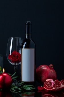 Wine bottle with rose in goblet, candle, pomegranate and plant