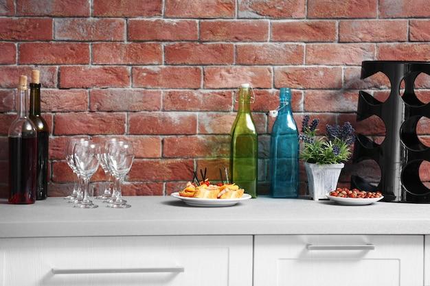 와인 병 및 벽돌 벽에 식탁에 canape