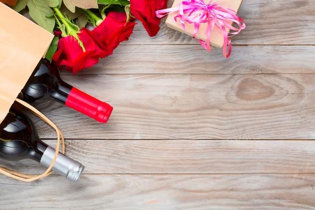 Винные бутылки и розовые цветы на деревянном столе