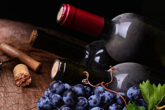 木製の表面にワインボトル、コルク、ブドウ