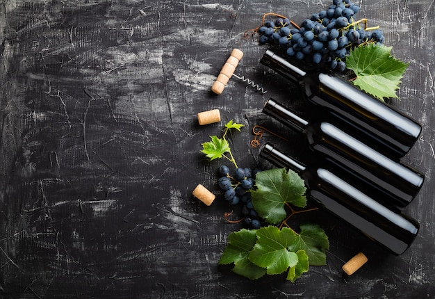 Wine bottles, grapes, grape bunches with leaves and vines corkscrew wine corks on dark rustic concrete background. flat lay wine composition with copy space on black stone table.