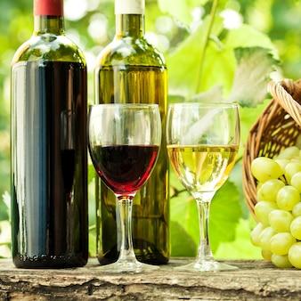 春にブドウ園に対してバスケットにワインボトル、2杯のグラスとブドウの束