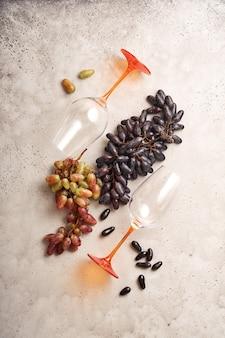 복사 공간이 있는 오래된 회색 콘크리트 테이블 배경에 포도와 와인잔이 있는 와인 병. 포도 나무 가지와 레드 와인입니다. 소박한 배경에 와인 구성입니다. 조롱.