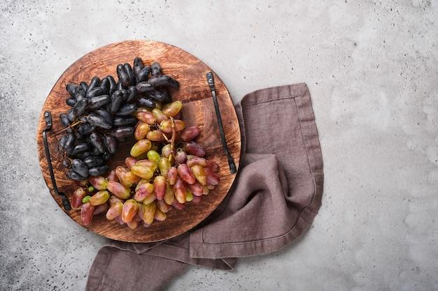 コピースペースと古い灰色のコンクリートのテーブルの背景にブドウとワイングラスのワインボトル。つるの枝を持つ赤ワイン。素朴な背景のワイン組成。モックアップ。