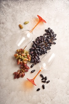 Wine bottles with grapes and wineglasses on old gray concrete table background with copy space. red wine with a vine branch. wine composition on rustic background. mock up.