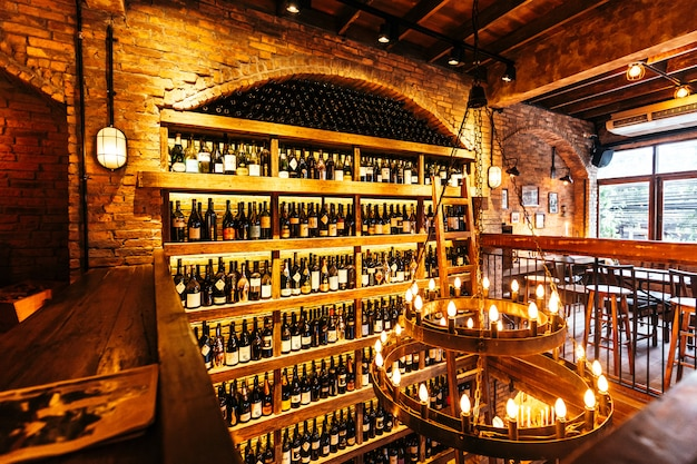 Wine cellar on the wall in italian restaurant decorated with brick in warm light that created cozy atmosphere.