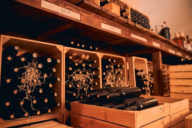 Wine cellar with bottles of alcoholic drink in wooden boxes and shelves with vintage year labels