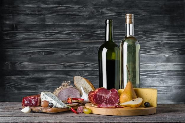 Вино, сыр и мясо на деревянном деревенском столе