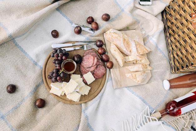 ピクニックで公園の木製のテーブルにワインチーズ、ブドウ、バゲット