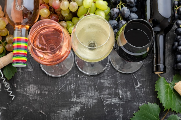 Wine choice degustation tasting. white wine rose red types wine in glasses and bottles. different varieties grapes. wine composition with on dark moody stone background. mediterranean drinks bar.
