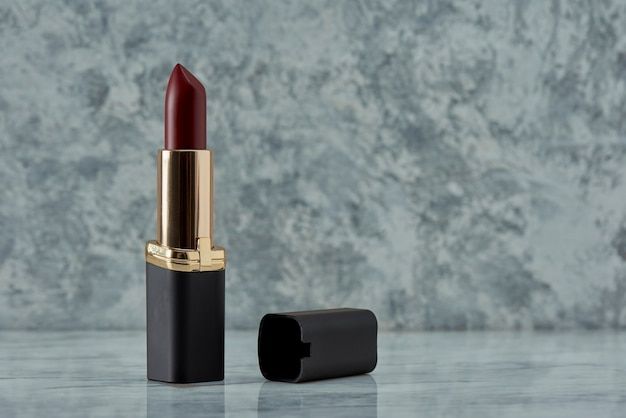 Wine colored lipstick with black on a marble surface with a background of white with black