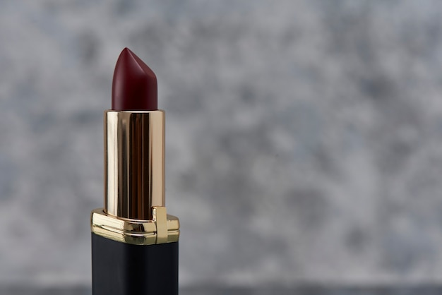 Wine colored lipstick with black on a marble surface with a white background with gray