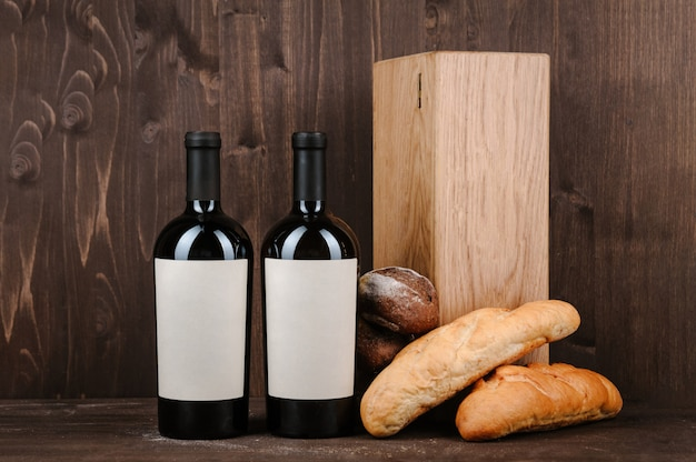 Wine composition with bread, two bottles in box and wineglass on wooden table