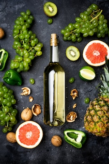 Wine concept. bottle and glass of young white bio wine with green grapes, grapefruit and other fruit on a gray stone background