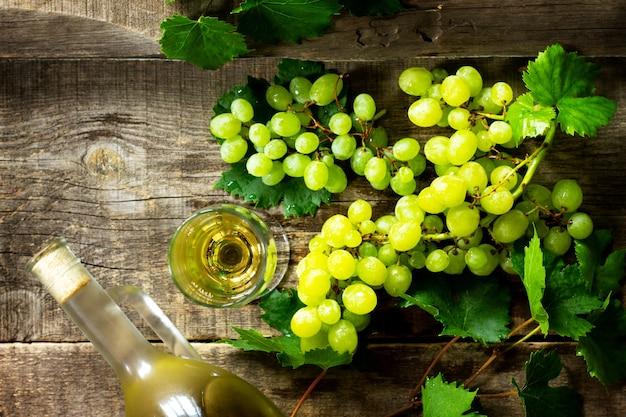 Концепция вина белое вино в бокалах, бутылка винограда на винтажном фоне.