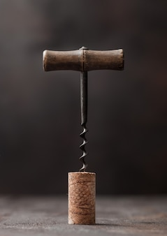 Wine cork with vintage corkscrew on top on wooden table background.