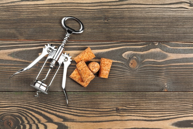 Wine corks with corkscrew on wooden table