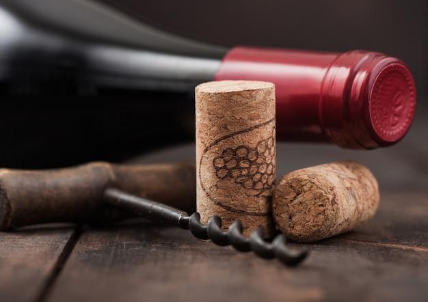 Wine corks with vintage corkscrew on wooden board background.