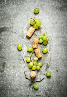 白ブドウとワインのコルク。石のテーブルの上。