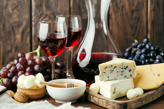 Wine and different cheese on wood