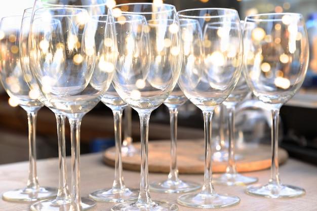 ぼやけた光の背景とバーのテーブルに並んでワインの空の透明なメガネお祭りのコンセプト