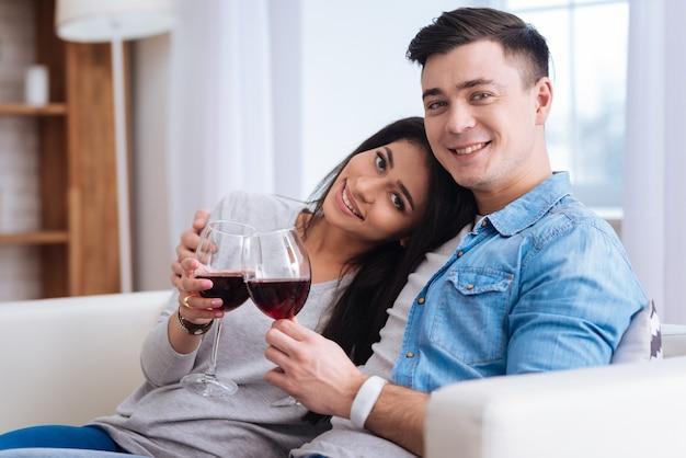 気分のためのワイン。カメラを見ながらワインとグラスを持って元気いっぱいのカップル
