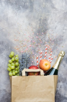 Wine, fruits, flowers (set for the party or picnic) in a paper craft pack on a gray concrete background. top view.