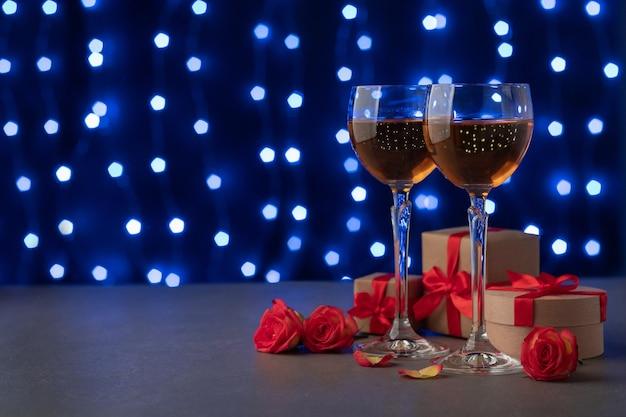 ぼやけたフェアリーライトの背景に対してテーブルの上のワイン、ギフトボックス、バラ。休日のお祝い