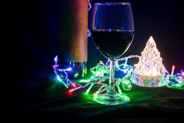 검은 배경에 빛나는 보케 화환에 와인 잔, 병, 크리스탈 크리스마스 트리. 확대
