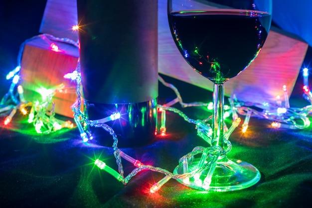 검은 배경에 빛나는 화환 보케의 와인 잔과 병