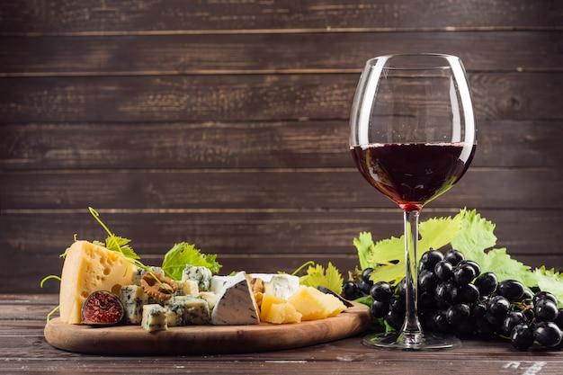 Бокал вина и гроздь винограда на деревянном столе