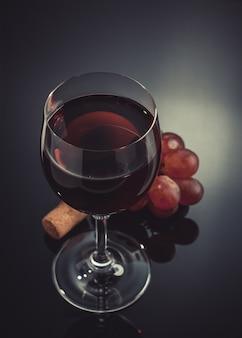 검은 배경에 와인 글라스와 포도