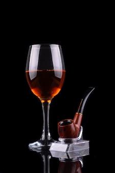 Бокал вина и курительная трубка на черном фоне