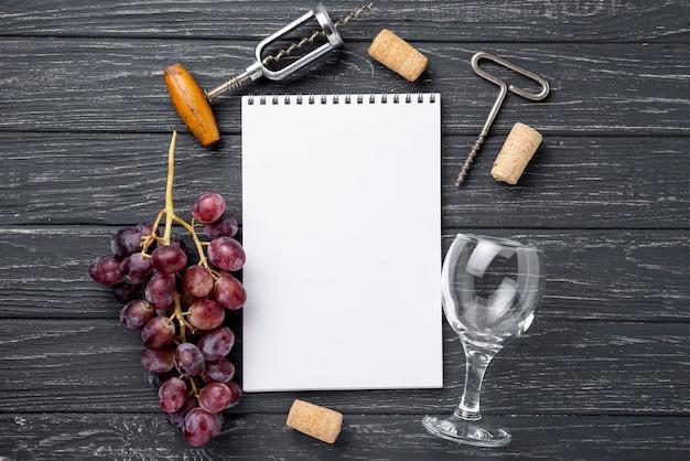 テーブルの上のノートの横にあるワイングラス