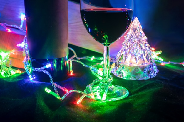 Wine glass and bottle and crystal christmas tree in shining bokeh garland on black background