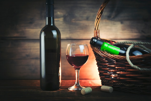 Wine on the glass and bottles on basket