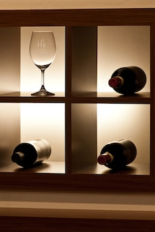 Wine glass and bottles in store show stand, dark light setup