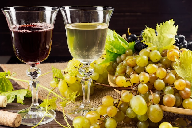 Wine glass and bunch of grapes on wooden table