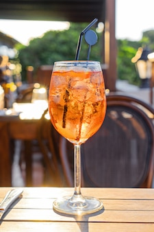 Wine glass of cold cocktail aperol spritz on table