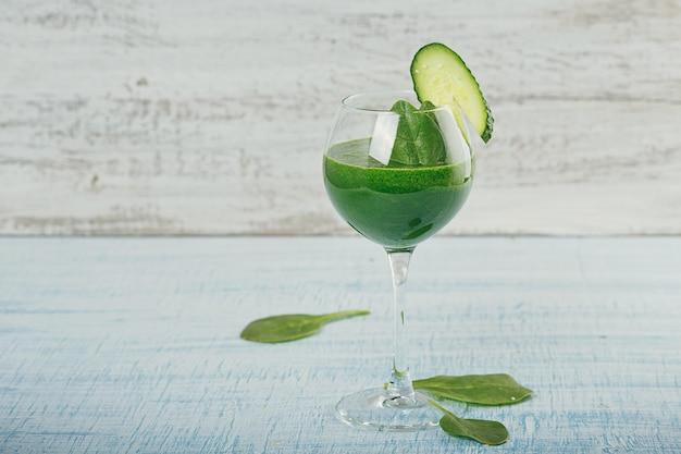 水色の木製の背景に新鮮な緑のほうれん草とキュウリのスムージーで満たされたワイングラス。ノンアルコール飲料。健康食品と菜食主義の概念。
