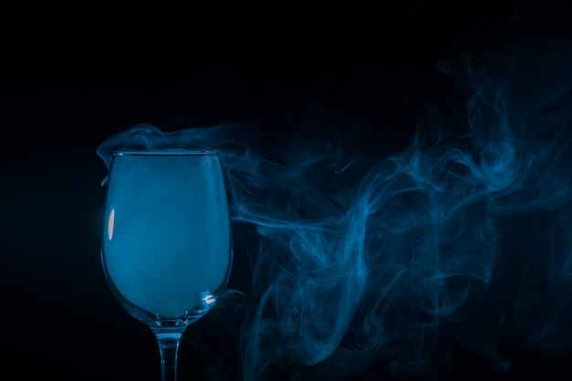 Wine glass filled with smoke on black
