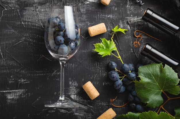 Wine glass full of grapes inside. wine bottles, grape bunches with leaves and vines wine corks on dark rustic concrete background. flat lay wine composition on black stone table.