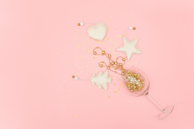 Wine glass poured out golden christmas decoration and confetti stars on pink new year, christmas, holiday concept