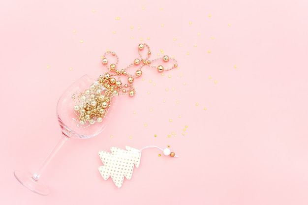 Wine glass poured out golden decoration, christmas tree and confetti stars on pink background. new year and christmas concept