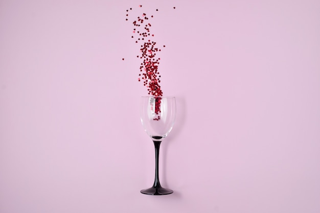 Wine glass poured out red heart confetti on pink color paper background.