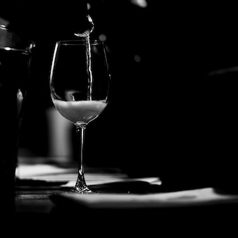 The wine glass stands on the table and a trickle of champagne is poured into it. bw.