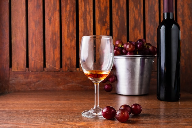 Wine glass and wine bottle with red grapes on wooden background