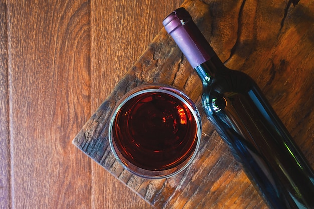 Wine glass and  wine bottle on the wooden table